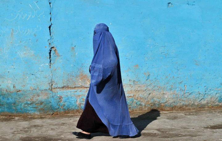 En människa, som bär burka, går på gatan. Vi kan inte se hennes ansikte.