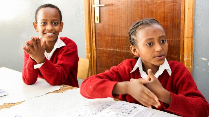Kaksi kuurojenkoulun oppilasta koulutöiden ääressä, toinen lapsista viittoo, toinen lapsista hymyilee..